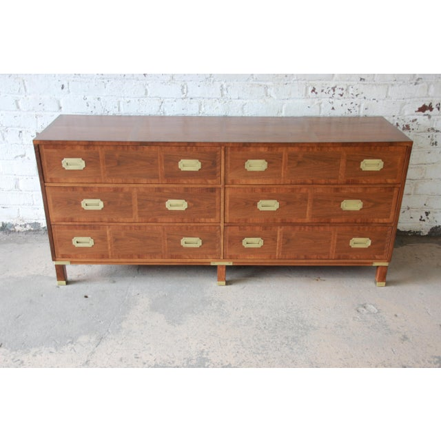 Offering a stunning newly refinished mid-century Hollywood Regency Campaign style dresser or credenza from the Milling...