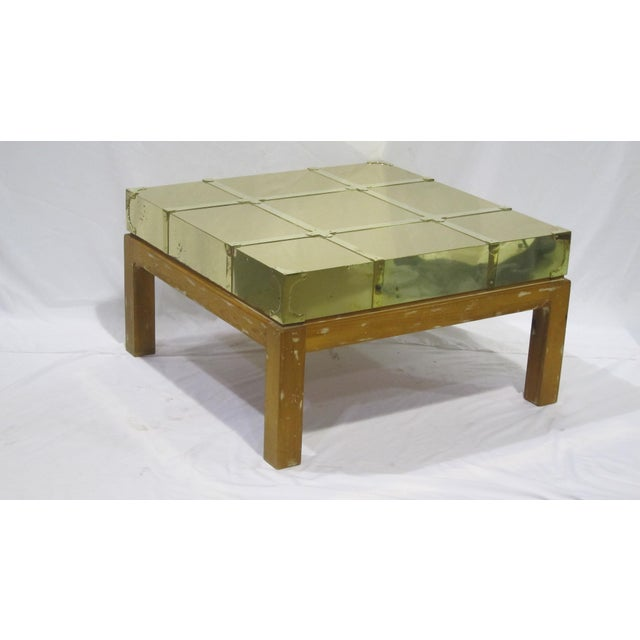 Estimate Retail Price: $1425. Gently worn brass and pine cocktail table with character marks. Each Sarreid LTD vintage...