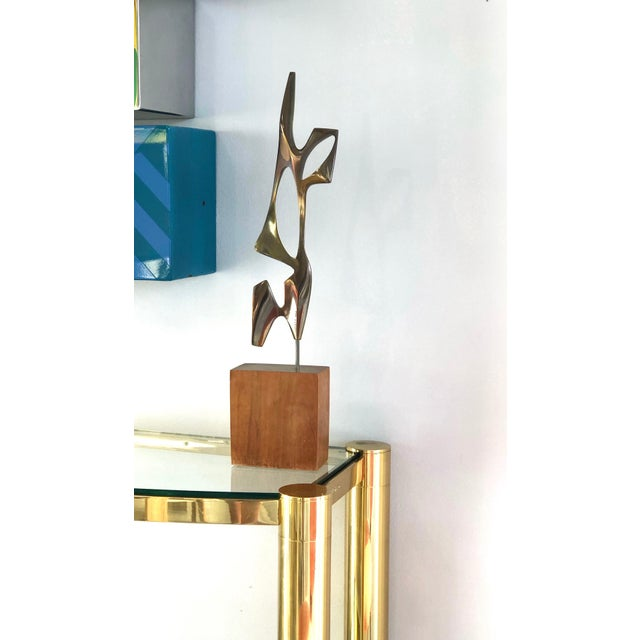 A modernist bronze sculpture on a wood base. Intriguing interplay of negative space with the chosen medium that creates a...