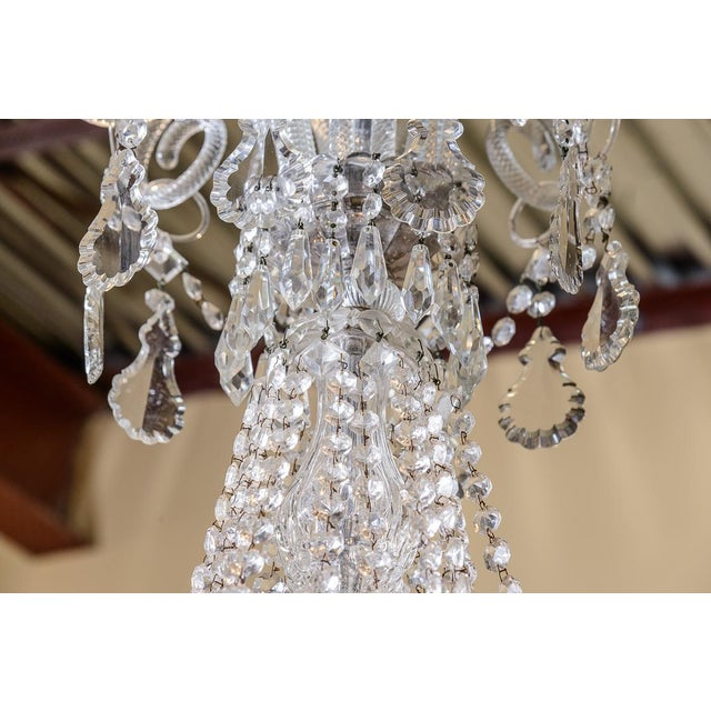 Pair of beautiful cut crystal chandeliers surmounted by a coronet of ten blown , spiral- twist, and scrolled crystal rods...