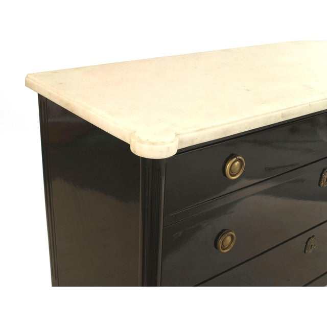 French 1940s 'Louis XVI style' ebonized and bronze trimmed chest with three drawers having ring handles under a white...