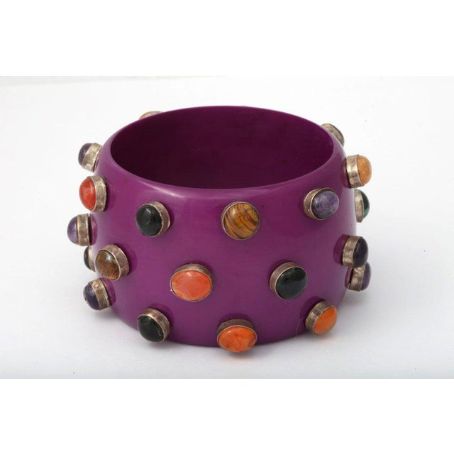"Dramatic purple bangle adorned with 27 small semi precious stones. Inside diameter is 2 5/8"". Due to the unique nature of..."