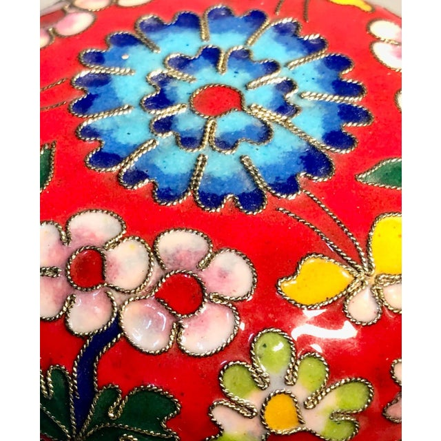 A luscious, enameled brass Chinese box with lid. Covered with shades of pink, blue, yellow and green on a red-orange...