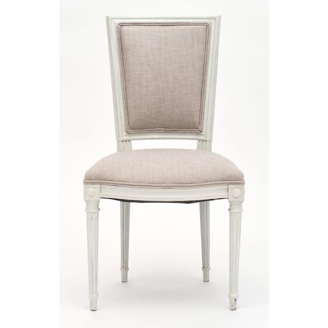 Set of six Louis XVI style painted dining chairs newly upholstered in a light gray linen blend. We love the beautiful...