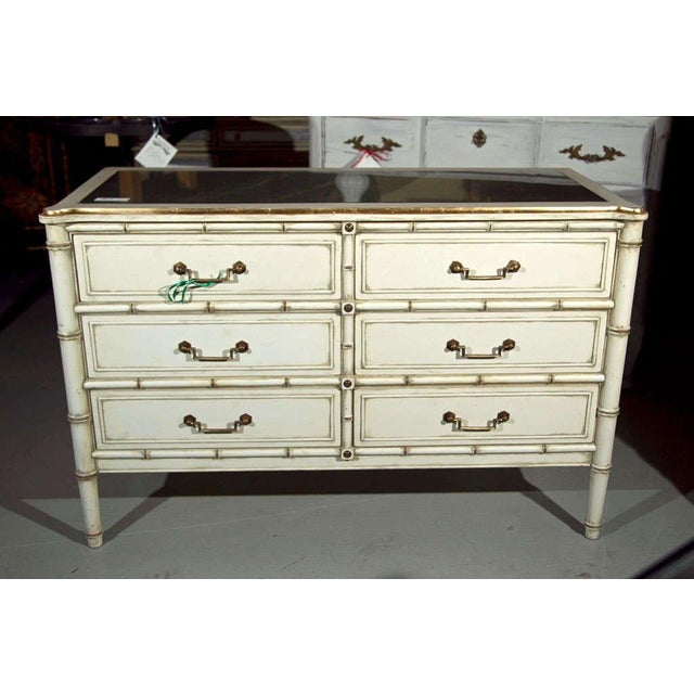 A white painted & parcel-gilt faux bamboo dresser, circa 1960. The silver-leafed glass top over a conforming case fitted...