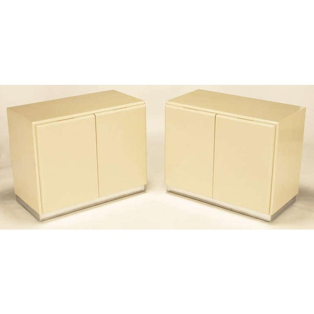 Pair of clean lined two-door cabinets in ivory lacquer on chromed metal over wood bases by Milo Baughman for Thayer...