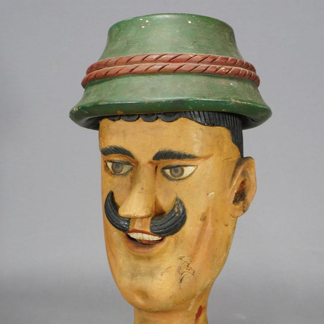 a large wooden carved head of a bavarian folksy man. may have been a decoration for a carnival booth or a folk festival....