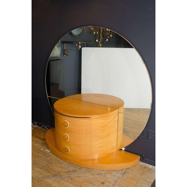 An Art Deco vanity or dressing table, circa 1930s in beechwood with large round mirror, curved drawers, apple juice...