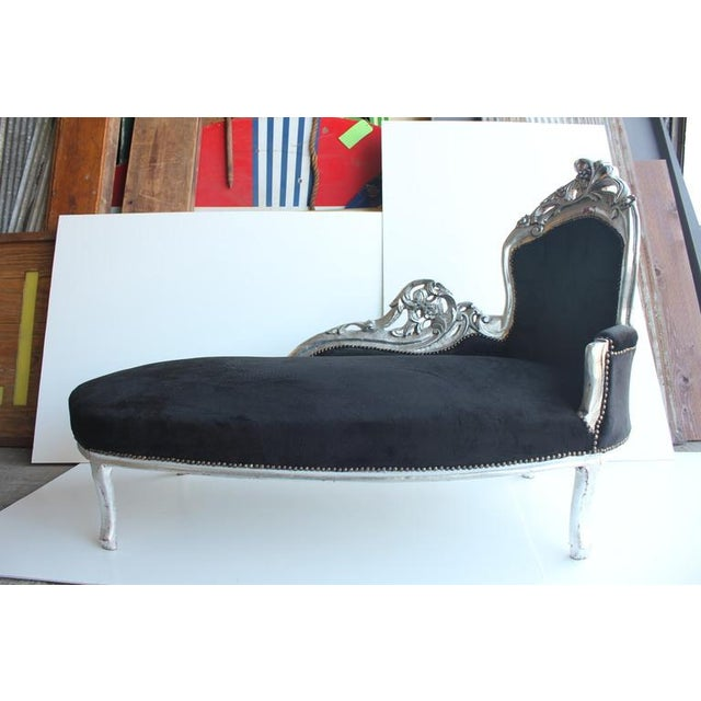 French 19th Century chaise longue with hand carved wooden base and velvet upholstery. The back is tufted.