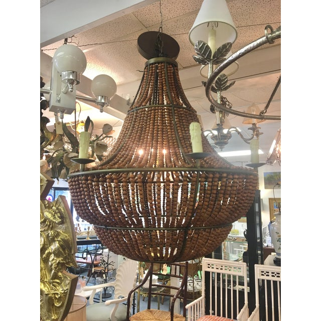 Mid century modern dramatic wood beaded chandelier. 4 tier taper with alternating wood toned beads on top tier. 6 lights....
