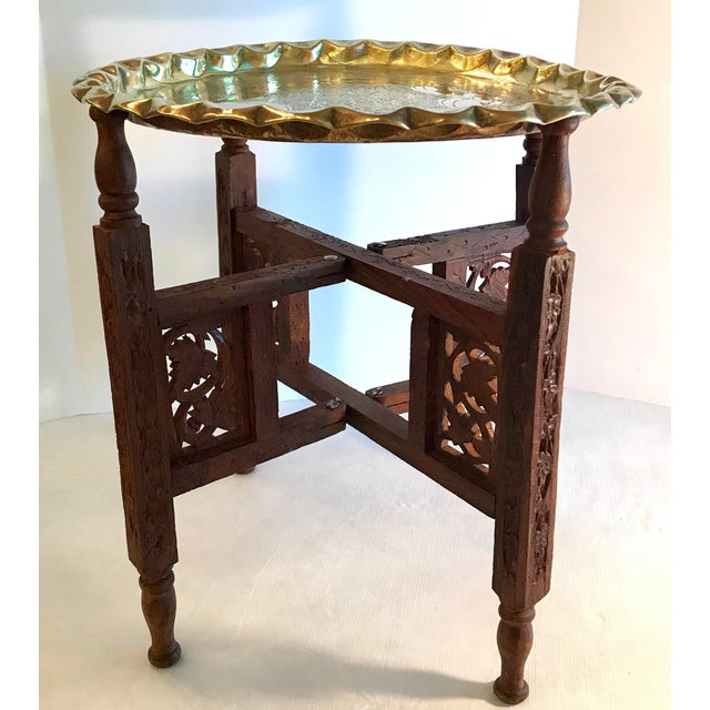 Beautiful carved wood campaign style table with detachable brass tray top. Nice detail on the legs which fold up. Tray...