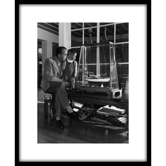 """In a quiet moment with his son, Stephen, Humphrey Bogart views a model of his yacht, the """"Santana,"""" 1952. 11"""" x 14"""" silver..."""