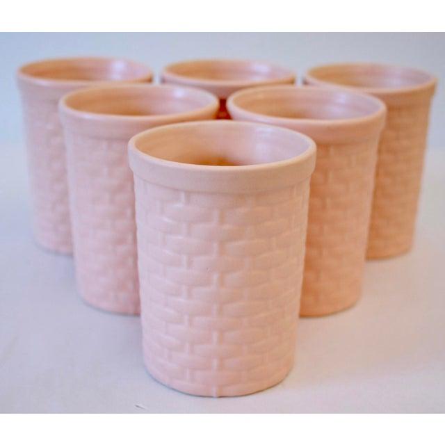 "Wonderful set of six peach matte glazed pottery basketweave motif tumblers. Each marked ""C"" to base."