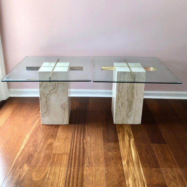 Gorgeous pair of travertine, brass and glass topped end tables. Made in Italy, circa 70s for Artedi. The glass tops are...