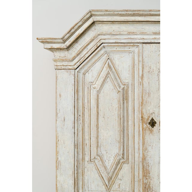 An important and richly carved Swedish armoire or linen press cabinet from the Baroque period with handsome ball feet,...