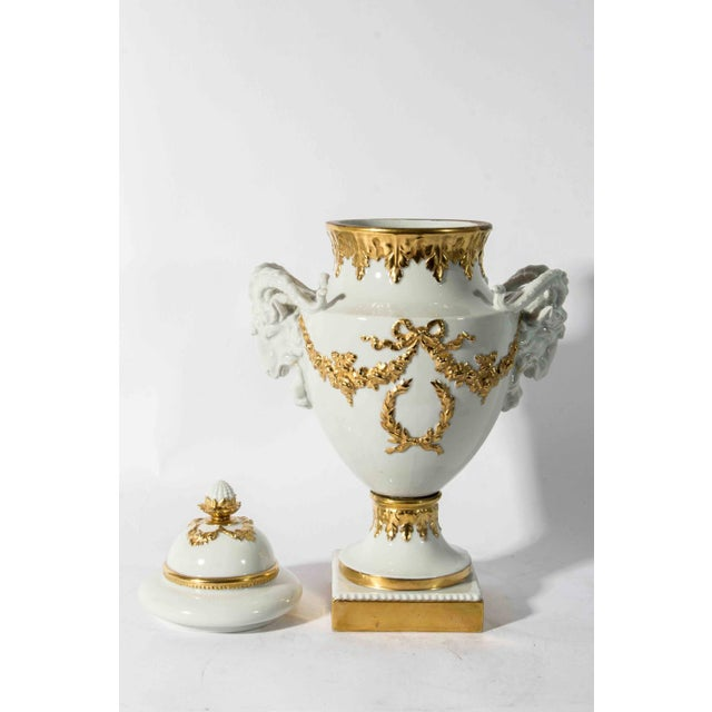 Antique English porcelain and gold urn shaped vase with lid, pedestal detail and ram shaped handles. In excellent...