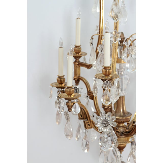A large rock crystal and ormolu Louis XV style chandelier, nine (9) lights on three (3) tiers, with central post of ormolu...
