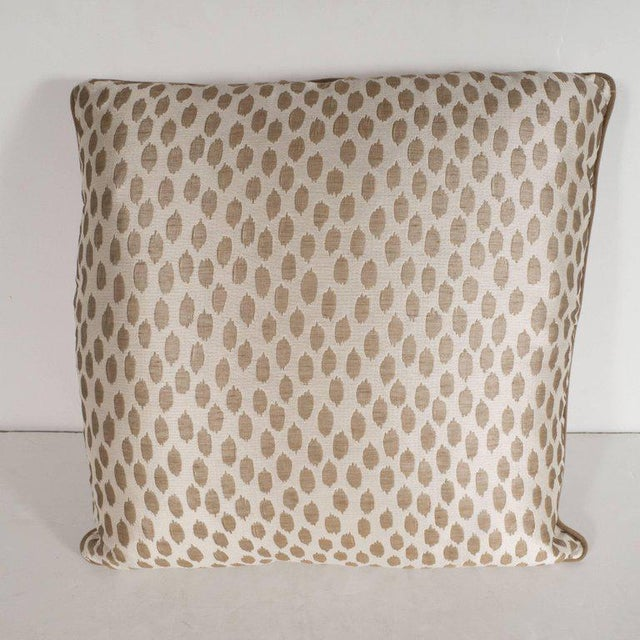 This elegant pair of square modernist pillows features organic forms in muted gold hue- with piping in a matching tone-...