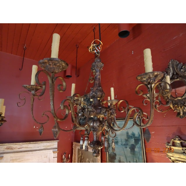 A beautiful Italian chandelier from the 18th Century. 6 lights. US wired. Scrolled iron arms with different shape tassels....