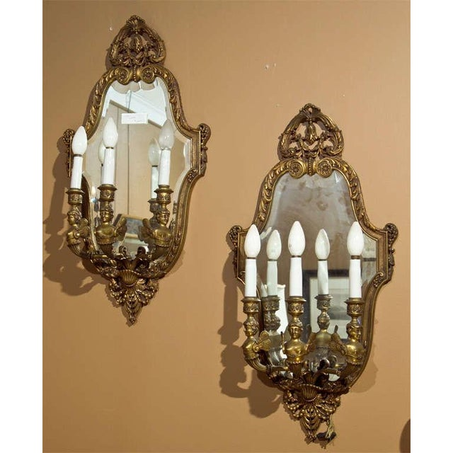 Pair of Neoclassical style bronze girandole wall sconces, the fine bronze frame with mirror back and three arms decorated...