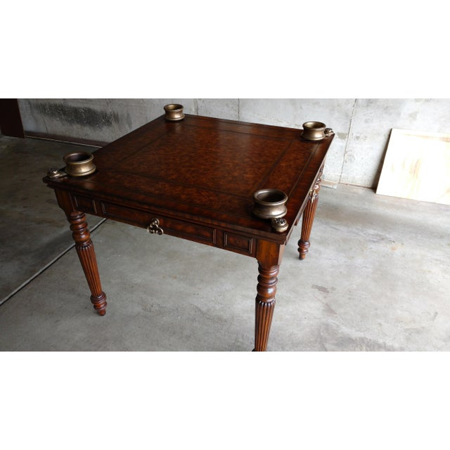 A vintage style Maitland-Smith game table. The table features unique brass cup holders that swing out from the corners....