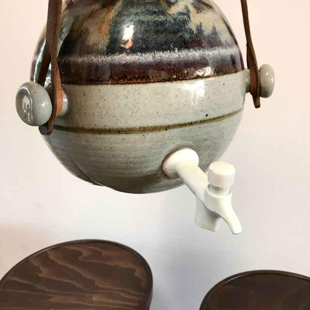 Hanging ceramic vessel with leather straps, driftwood details and brass rivets. Removable cork top and functional spout. A...