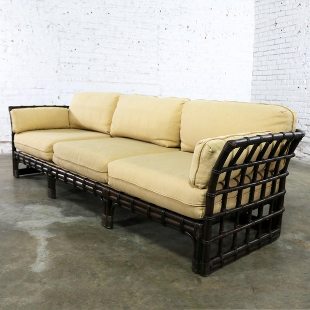 Handsome windowpane style rattan sofa by Brown Jordan with straw colored upholstered cushions. It is in wonderful vintage...