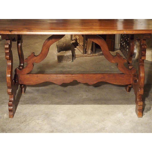 From the 19th Century, this table from Tuscany has a top with arched corners and a wonderful shaped wooden stretcher....