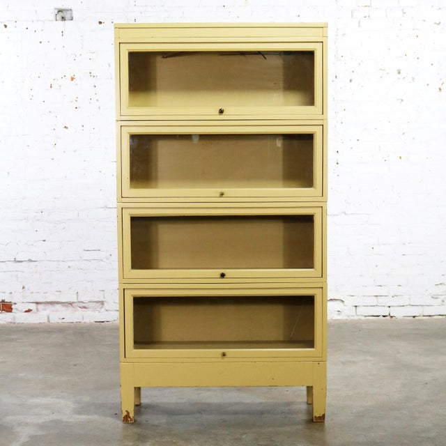 Handsome vintage Globe Wernicke industrial stacking barrister bookcase with a distressed golden yellow painted finish to...