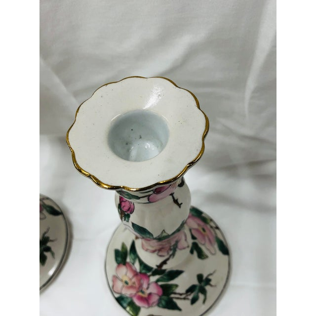 Hand painted pink dogwood pattern candlesticks. Gilt adorns the top edge. Marked Andrea by Sadek.