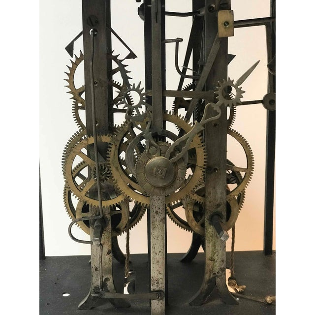 Clock works from 19th century long case clock mounted on stand as sculpture.