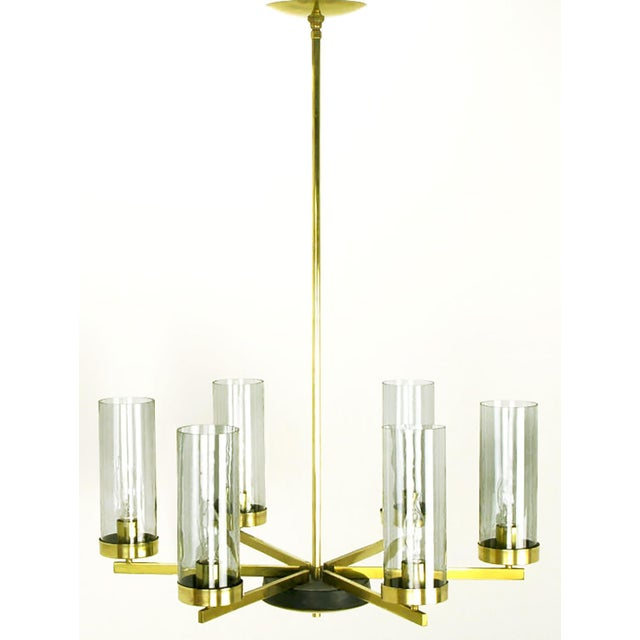 Attributed to Lightolier, this six-light chandelier has brass flat bar armature and smoked glass cylindrical hurricane...