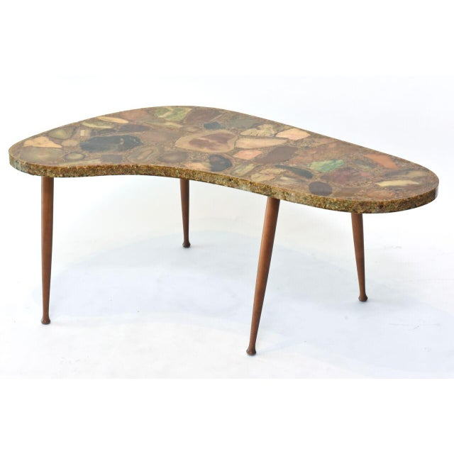 The kidney shaped top with different chunks of specimen marbles laid in a resin ground over splay walnut tapering legs.