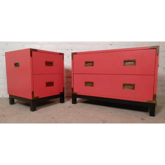 Set of vibrant campaign style dressers with brass hardware and heavy black iron bases. The color is a vivid red which is...