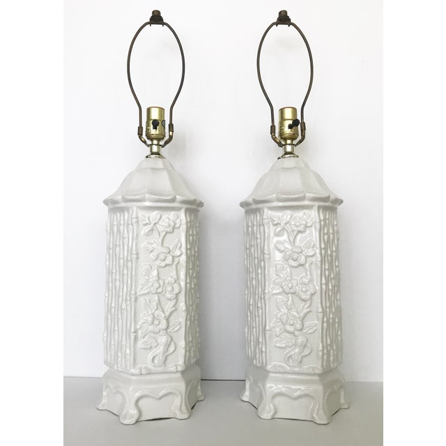 Vintage pair of chinoiserie white ceramic pagoda style lamps. Floral and faux bamboo columns with pagoda tops. In good...
