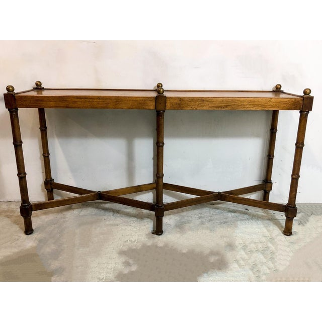 1970s faux bamboo console table with double cross stretchers. It was manufactured by Brandt and is marked on the underside.