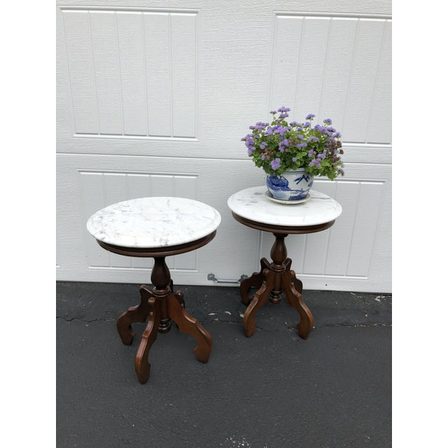 A pair of Italian marble top accent tables. Each table features a round, beveled top of white Italian marble with gray...