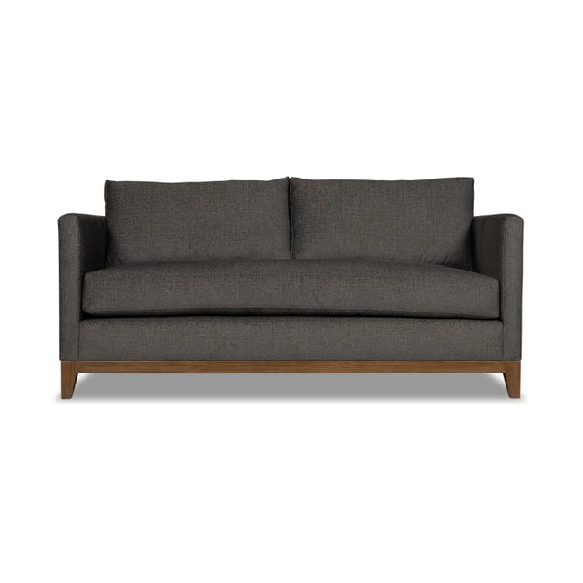 Fully upholstered in a Crypton fabric for durability and elegance, this loveseat, set on a wooden base and legs, is a...