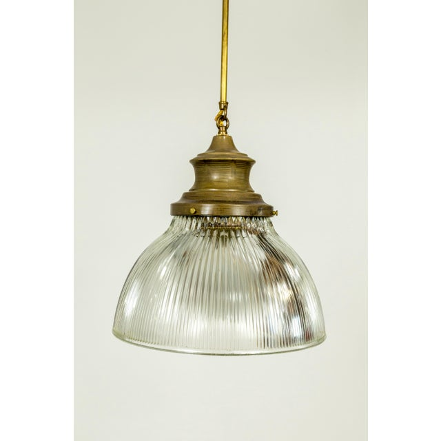 Large, thick, holophane glass pieces from the early 20th century, newly fashioned into pendant lights with brass glass...