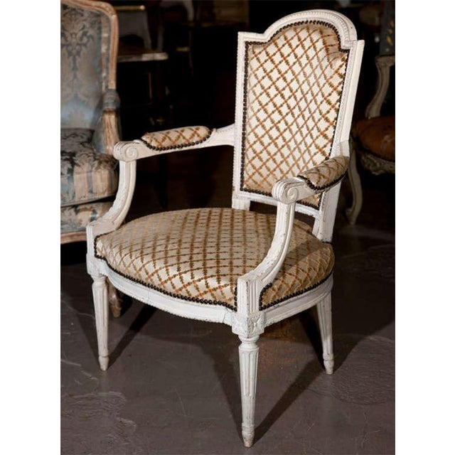 Pair of French Louis XIV style armchairs. Distress painted in white. Circa 1950s. Upholstered in lattice pattern fabric,...