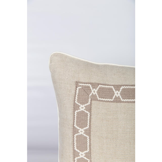 Custom oatmeal-and-ivory linen lumbar pillow with fretwork pattern tape on front, solid oatmeal linen back and...