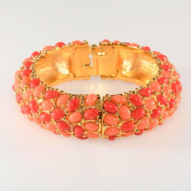 Kenneth Jay Lane two-tone hinged bangle bracelet embellished with two shades of glass coral colored cabochons. Metal is...