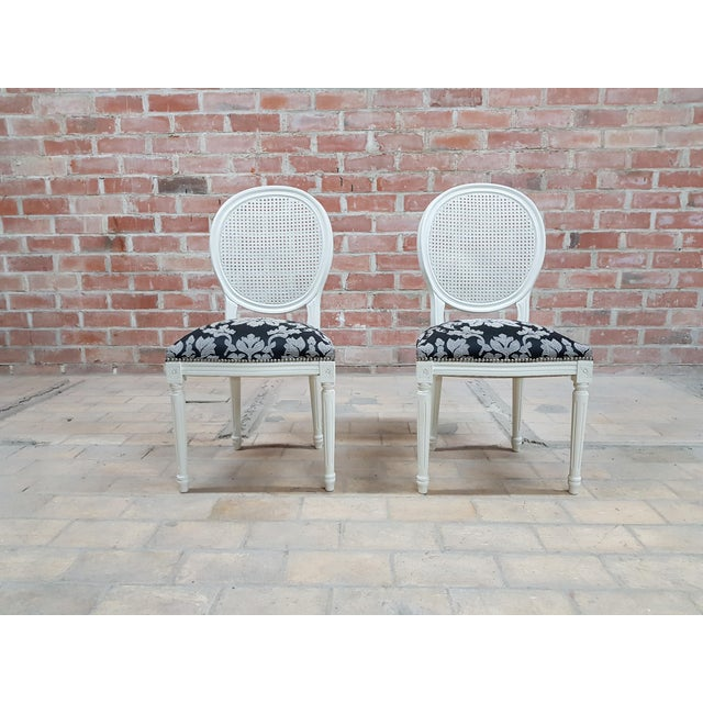 Luxurious pair of vintage Louis XVI Style French newly upholstered white Shabby Schick medallion cane back accent chairs...
