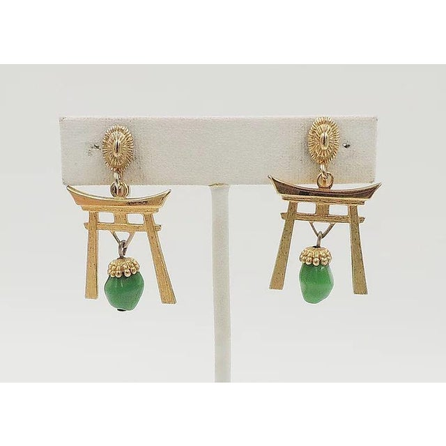 """1960s goldtone pagoda with faux-jade rhinestone drops clip back earrings. Marked """"Napier."""" Measure: 1.5 inches L x 0.94..."""