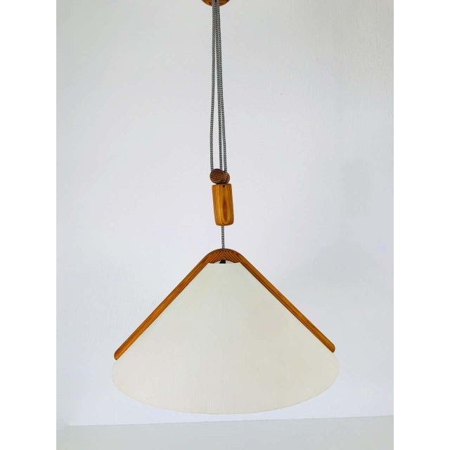 A wooden pendant lamp by Domus made in the 1960s. The body of the lamp is wood. The lamp has a Scandinavian design.