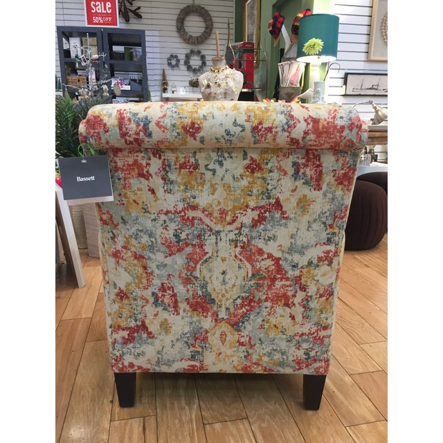 Small accent chair with upholstered back and tapered wooden legs. Multi-colored fabric includes shades of blue, red and...