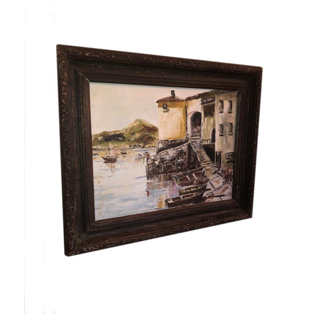 A vintage nautical painting of a French seaside fishing village. From France, in a dark wood frame.