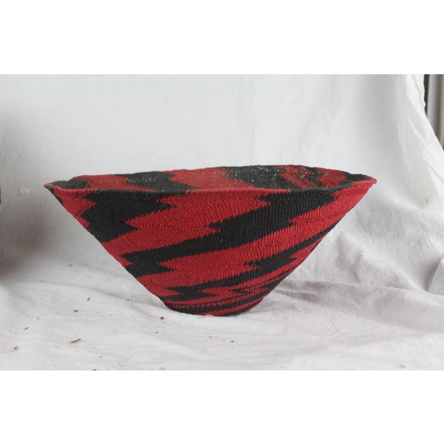 Handwoven Zulu telephone wire jagged-swirled tribal basket in red and black. Made in the mid 20th century.