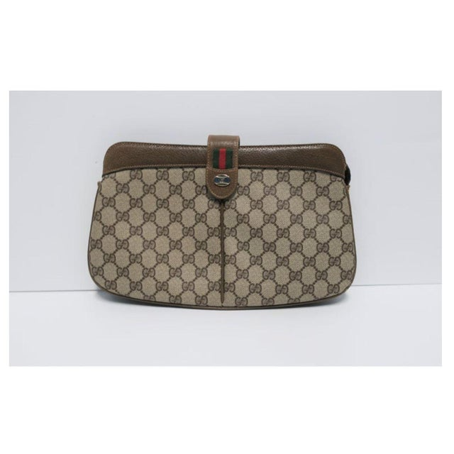 A Vintage classic authentic Gucci clutch handbag featuring its iconic 'G' tan canvas, tan/brown leather trim and piping,...
