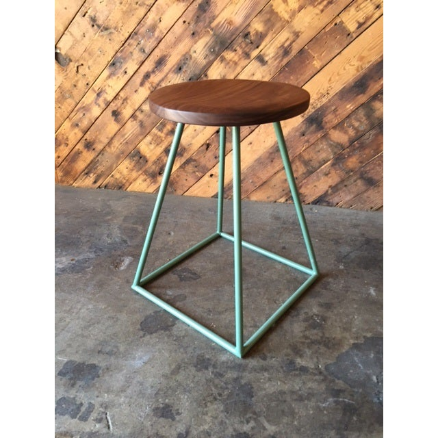 Custom stool featuring a geometric, sage green-painted steel base and a hand-shaped, solid walnut seat. L:14.75 D:14.75...